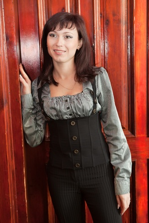 An attractive brunette woman in casual clothing leaning photo