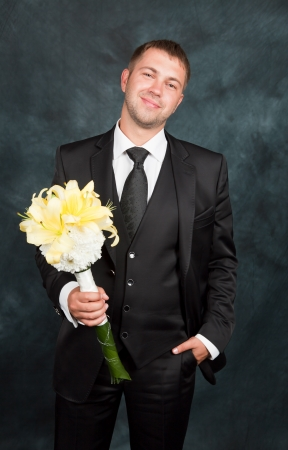 A young groom with a bouquet in studio photo