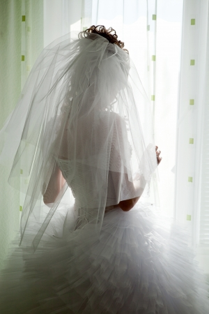 Bride silhouette looking through window Stock Photo