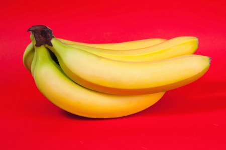 Bunch of bananas on red background photo
