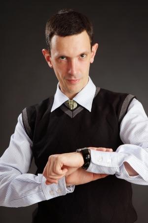 watch over: Businessman looking on his watch over dark grey background