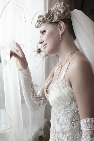 honey blonde: The bride in expectation of the groom looks out in a window Stock Photo