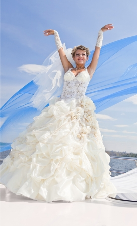 The beautiful bride on the yacht in solar and bright day in the blue sky photo