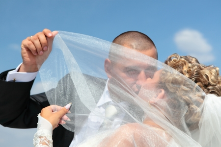 passionately: The groom and the bride passionately kiss under a veil against the blue sky in a sunny day