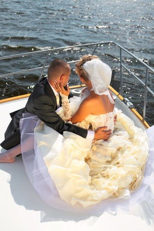 Happy newly-married couple floats on the yacht at ocean in a sunny day