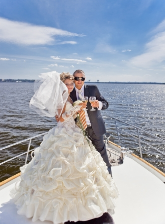 Happy groom and the bride with champagne on the yacht in solar and bright day