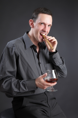 The guy with a cigar and cognac on a black background photo