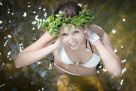 Portrait of young beautiful woman wearing a wreath of wild flowers Stock Photo - 15780322