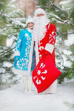 ded moroz: Russian Christmas characters  Ded Moroz  Father Frost  and Snegurochka  Snow Maiden  with gifts bag Stock Photo