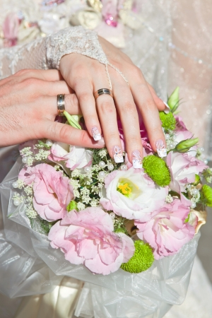 Hands and rings on wedding bouquet Stock Photo - 16596490