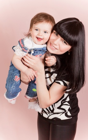 Happy joyful mother with laughing little daughte in studio photo
