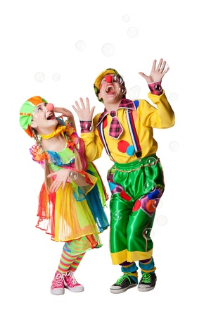 Two cheerful clowns  in the soap bubbles isolated on a white background