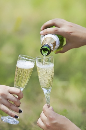 Champagne pour with two glasses in hands