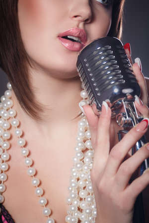 kareoke: Close up portrait of a young singer with a retro microphone on a black background Stock Photo