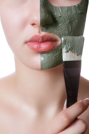 Young woman with facial mask in beauty spa isolated on a white background