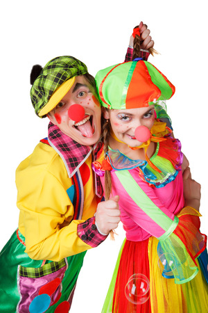 Two clown smiling isolated over a white background photo