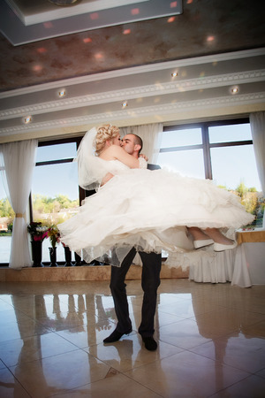 Kiss and dance young bride and groom in banqueting hall Stock Photo