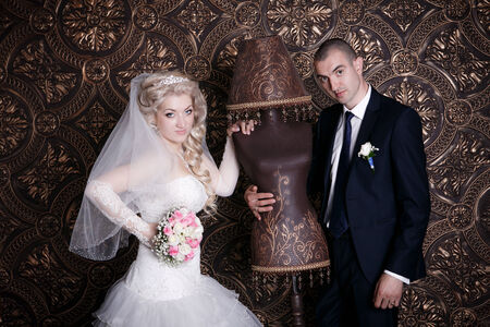 happy groom and the charming bride with a bouquet from roses in studio on a brown background photo