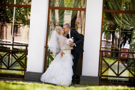 Bride and groom  near glass building photo
