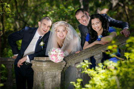 witness: Portrait of the groom, the bride and the best man with the witness in the park