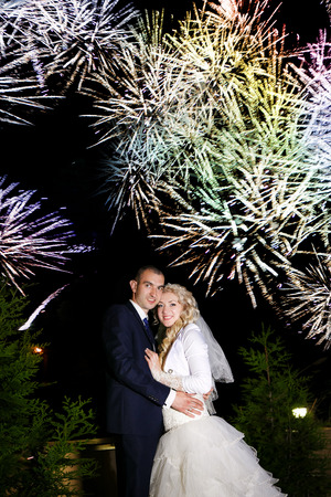 Bridal couple dancing sorrounding by fireworks photo
