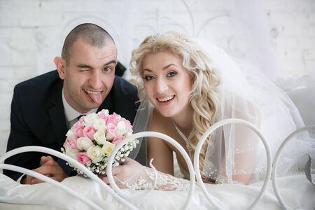 happy bride with a wedding bouquet from roses and the cheerful groom who is putting out the tongue, lie on a bed in bedroom photo
