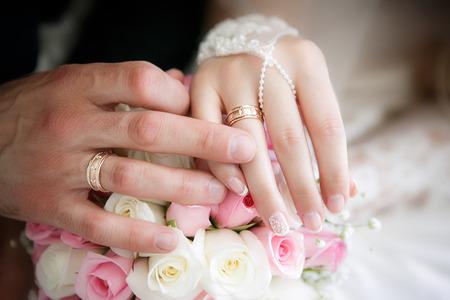 Handen van de bruidegom en de bruid met trouwringen en een bruidsboeket van rozen
