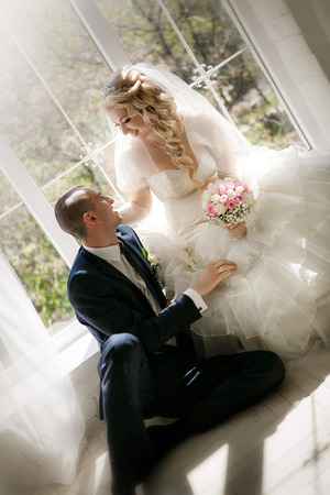 happy groom and the bride sit at a window