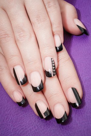 nail lacquer: Female hands with black manicure on the violet background