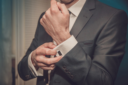 suit  cuff: groom putting on cuff-links as he gets dressed in formal wear close up