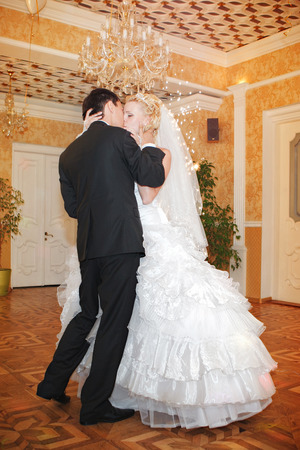 banqueting: young bride and groom kissing in banquet hall