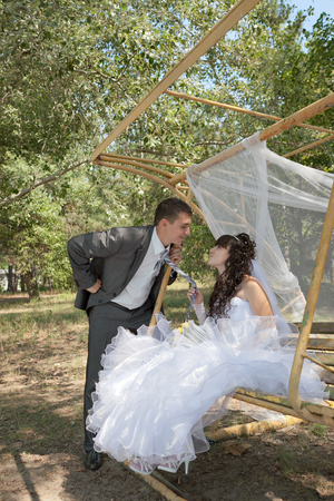 couple in love bride and groom on swing in park in their wedding day photo