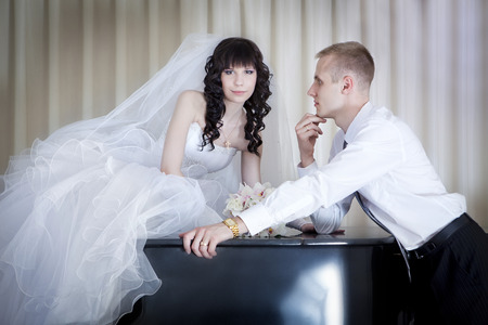 The groom and the bride near a grand piano photo