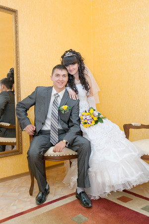 Bride and groom sitting on wooden chair photo