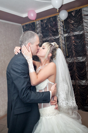 banqueting: Kiss and dance young bride and groom in banqueting hall Stock Photo