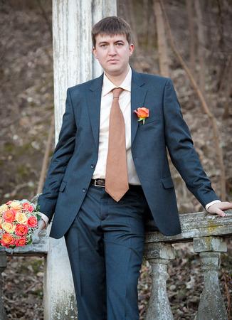 reciprocity: well-dressed groom standing near column Stock Photo