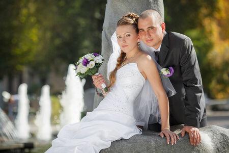 groom and  bride near the fountain photo