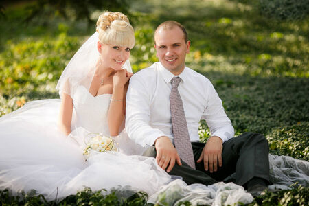twosome: Wedding - Bride and groom hugging and looking in the eyes of one another sitting at a green grass