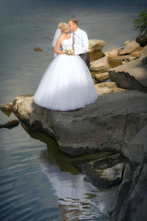 bride and groom on the banks of the river photo