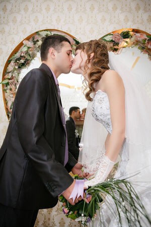 Kissing bride and groom in interior wedding palace photo