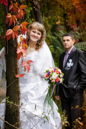 Just married couple with beautiful red autumn leaves in the background photo