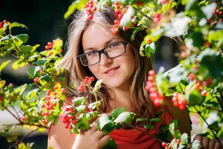 guelder rose berry: Portrait of a beautiful girl  in glasses near the red viburnum