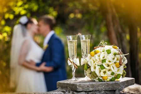 Trouwringen met rozen en glazen champagne en een kus van de bruidegom en de bruid op een achtergrond
