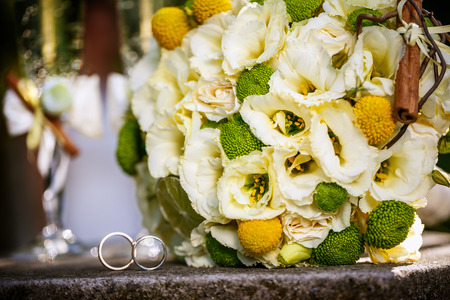 Wedding rings with wedding bouquet from beige roses, cinnamon, a lemon, a lime  and glasses of champagne photo
