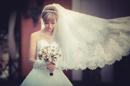 Portret van een mooie blonde bruid met een bruiloft boeket in de handen