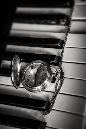 Pocket watch on old keyboard piano photo