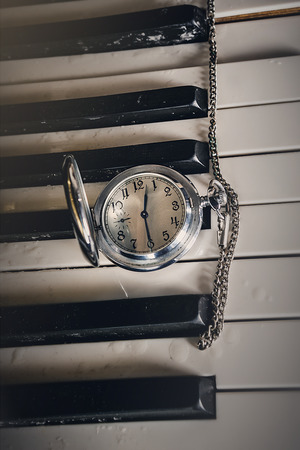 Pocket watch on old keyboard piano