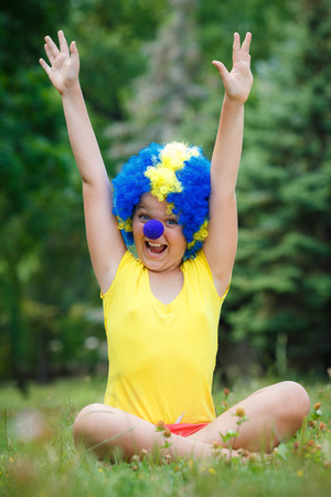 child kid girl with party clown blue wig funny happy open arms expression and garlands in the park photo