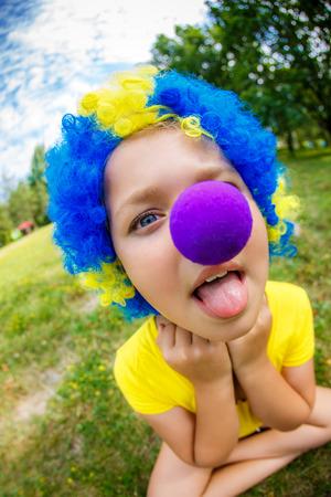 nariz roja: Muchacha divertida en peluca de payaso con nariz roja saca la lengua