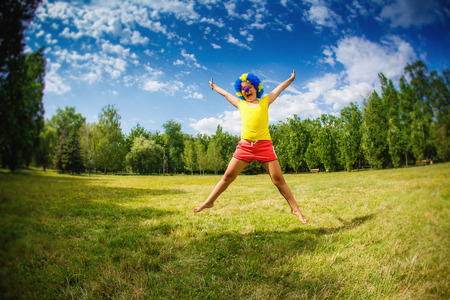 child kid girl with party clown blue wig funny happy open arms expression and garlands is jumping in the park photo